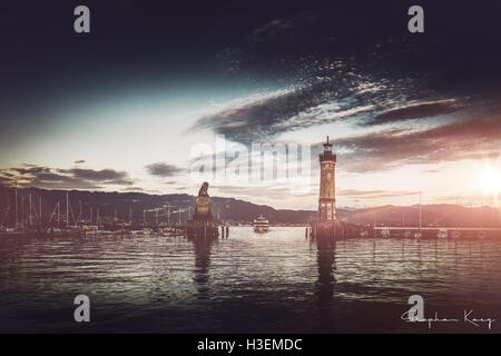 Sun sets on beautiful Bavarian harbor lighthouse with mountains behind it and clouds overhead - Stock Photo