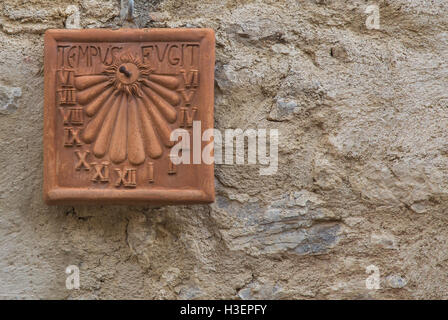 Sundial in clay attached to the wall with Latin inscription - Stock Photo