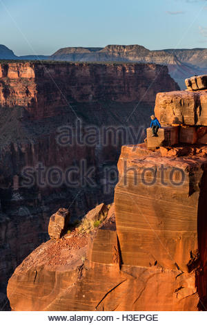 A hiker enjoys the sunrise from Toroweap Point above the Colorado River. - Stock Photo