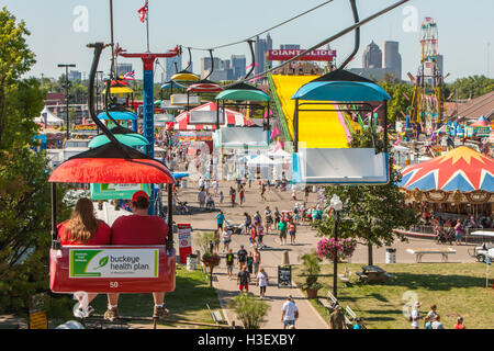 People enjoy attractions and rides on the midway of the Ohio State Fair, with the skyline in the background in Columbus, - Stock Photo