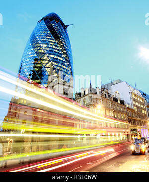 Red London bus passes 30 St Mary Axe,Gherkin,Swiss Re Building,City Of London,England at Dusk - Stock Photo