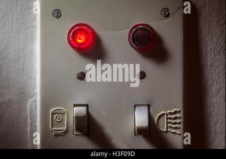 Details of an old dirty plastic switches for bathroom, red light is on for boiler. - Stock Photo
