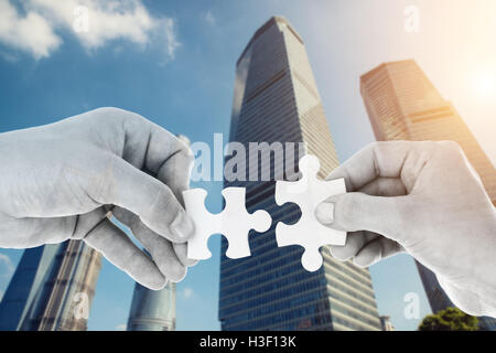 Hands putting partnership puzzle pieces together on skyscraper building in background. Partnership network concept - Stock Photo