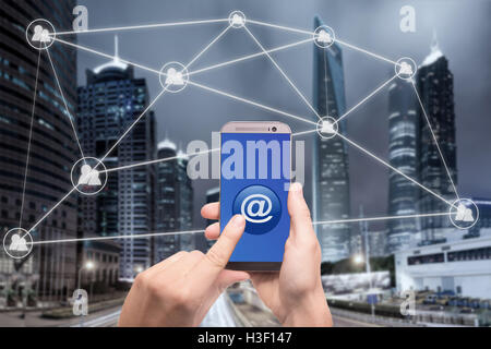 Hand holding smart phone and click on button with at sign linked with people icons. Email marketing, newsletter - Stock Photo