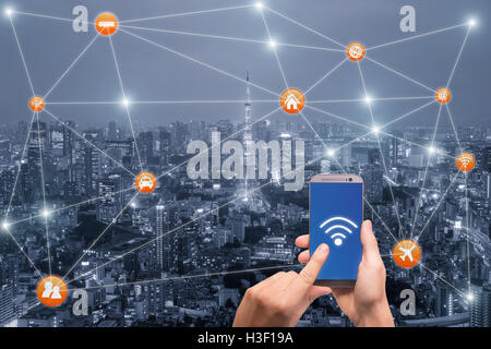 Hand holding smartphone with Tokyo city scape and wifi network connection. Smart city network connection concept - Stock Photo
