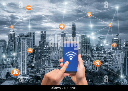 Hand holding smartphone with bangkok city scape and wifi network connection. Smart city network connection concept - Stock Photo