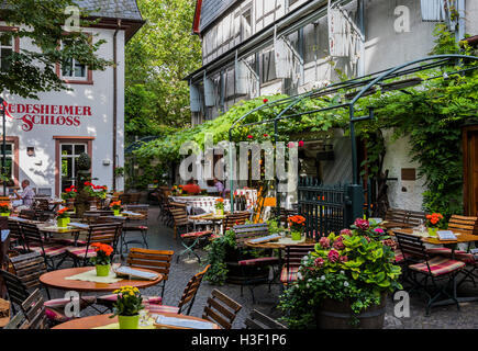 Rudesheim, Germany - August 20,2016: Terrace with wooden chairs and tables of Rudesheimer Schloss in Rudesheim near - Stock Photo