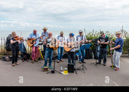 The Bay Boys, musical folk group of senior men playing guitars in the sunshine, together with a woman fiddle player, - Stock Photo
