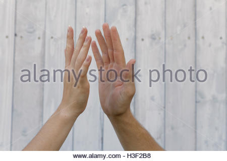 symbolizing hands: young woman and man clapping hands - Stock Photo
