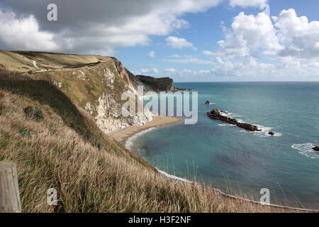 Looking out across 'Man of war' bay with tide out and the cliffs and rocks visible on a sunny day with blue sky - Stock Photo