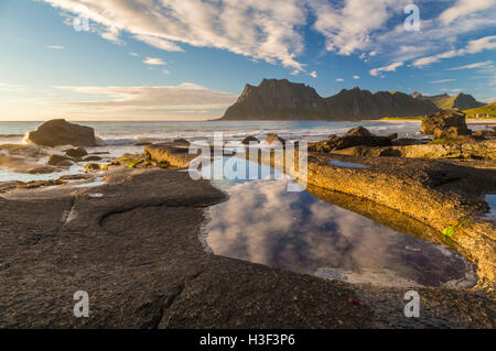 Rocks in evening light with warm light shining on them with sky reflecting in a pool of water, high mountains in - Stock Photo