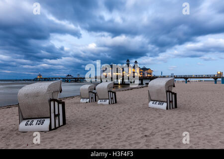Beach chairs in front of the illuminated pier of Baltic Sea resort Sellin, Ruegen, at dusk - Stock Photo