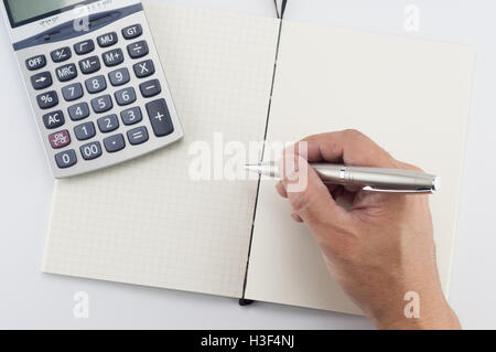Man hand with pen writing on notepad, on white background. - Stock Photo