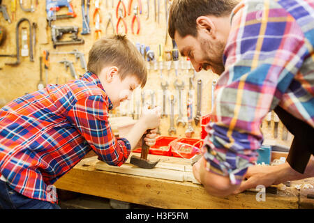 father and son with hammer working at workshop - Stock Photo