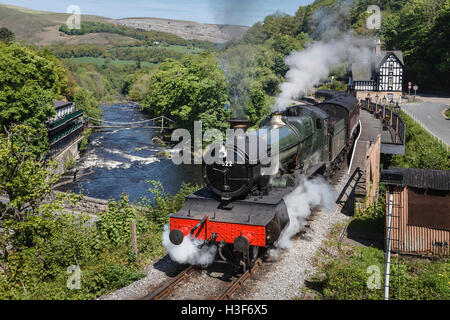 Train at Berwyn Station with a view of the River Dee and the chain bridge, Llangollen Railway, Denbighshire, Wales - Stock Photo