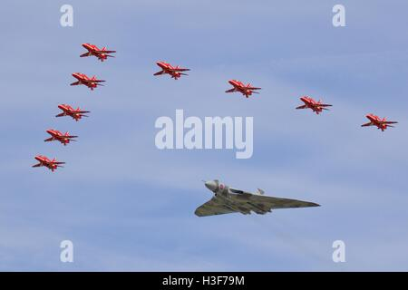 Avro Vulcan B2 bomber flying in formation with the Red Arrows at the Royal  International Air Tattoo - Stock Photo