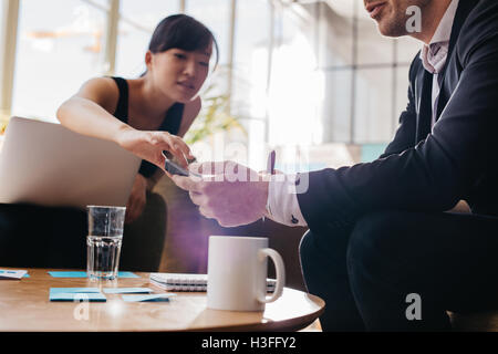 Cropped shot of young business people using mobile phone while sitting together in office lobby. Focus on hands - Stock Photo