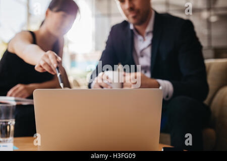 Shot of two businesspeople sitting together and working on laptop. Executives meeting in a office lobby. Woman pointing - Stock Photo