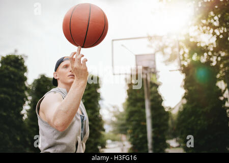 Young man balancing basketball on his finger on outdoor court. Streetball player spinning the ball. Focus on basketball. - Stock Photo