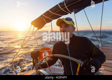 Skipper drives the sailing boat in the Aegean sea. - Stock Photo