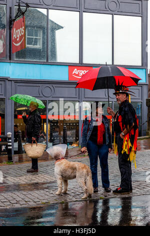 A Morris Dancer Shelters Under An Umbrella Whilst Waiting To Perform At The 'Dancing In The Old' Event, Lewes, Sussex, - Stock Photo