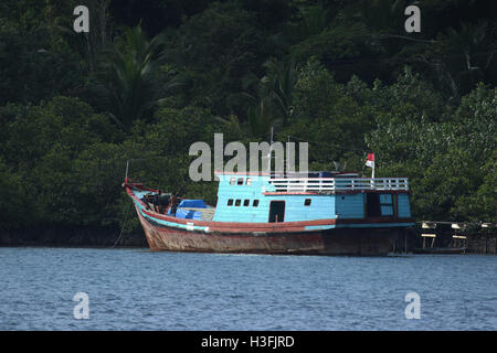 Old boat being repaired in the Mentawai Islands - Stock Photo