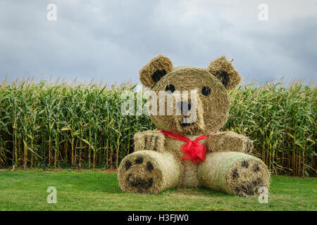 A giant teddy bear made out of straw bales in a farm setting. - Stock Photo