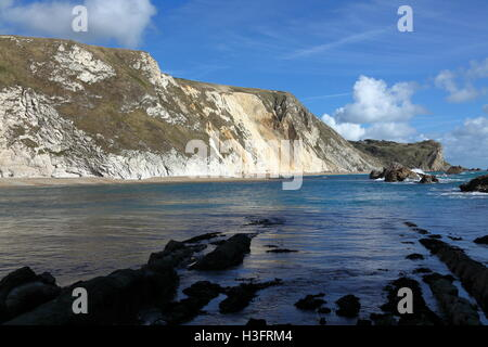 Looking across man of war bay at the high chalk cliffs above the blue waters of the bay with rocks sticking out - Stock Photo