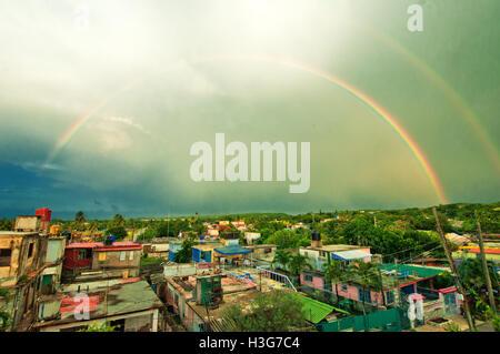 Rainbow over the town of Guanaba in Havana, Cuba - Stock Photo