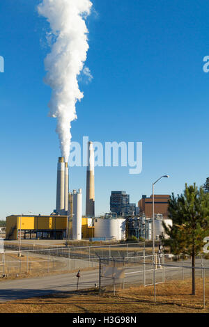 Entrance gate  of Duke Energy's coal fired  steam station on Belews Lake, North Carolina. Smoke billows from one - Stock Photo
