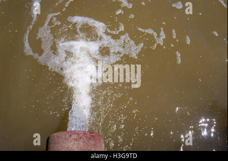 Water flowing from rusted metal culvert drain pipe opening and splashing into foamy brown water, viewed from above. - Stock Photo