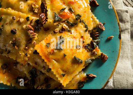 Homemade Pumpkin Ravioli with Butter Sauce and Savory - Stock Photo