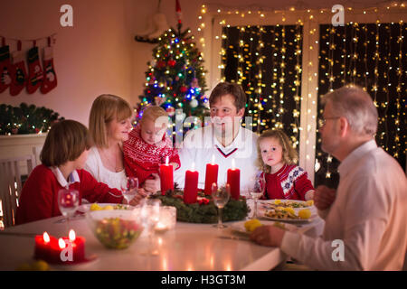 Big family with three children celebrating Christmas at home. Festive dinner at fireplace and Xmas tree. Parent - Stock Photo