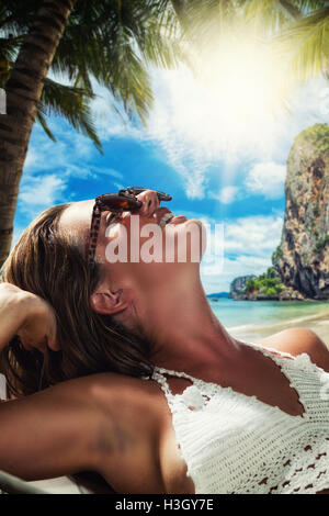 Young beautiful woman relaxing on the hammock under the coconut trees - Stock Photo