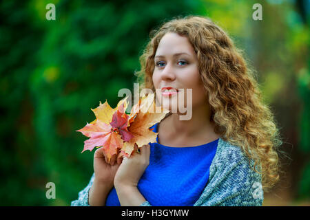 beautiful plus size model in the autumn park - Stock Photo