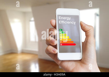 Energy efficiency rating on smartphone app by woman real estate agent and home interior in background - Stock Photo