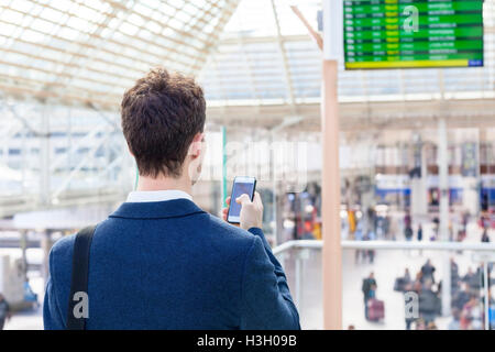 Traveler sending text message on smartphone with train timetable in background - Stock Photo