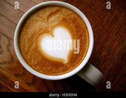 Heart latte art coffee on wooden background - Stock Photo