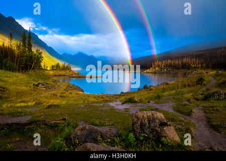 A double rainbow arches over Medicine Lake in Jasper National Park's Maligne Valley. - Stock Photo