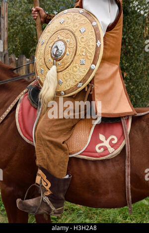 Detail of guard in traditional hun clothes with shield and spear on horseback Kazakhstan - Stock Photo