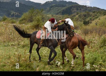 Kazakh men arm wrestling on horseback called Atpen Audaraspak in Huns Village - Stock Photo