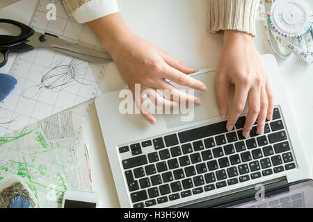 Hands working with a laptop, sewing accessories around Stock Photo