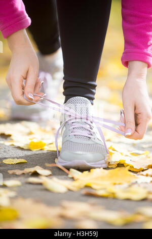 Hands tying trainers shoelaces on the fall pave - Stock Photo