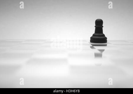 A black chess figure is reflected on a glass chess board. - Stock Photo