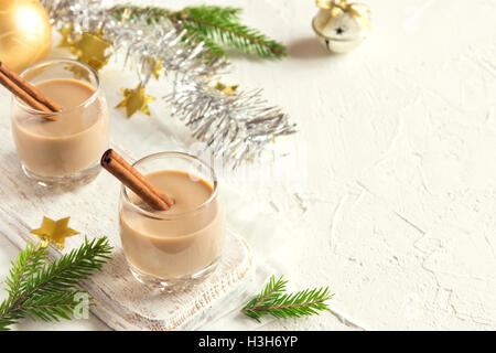 Chirstmas Eggnog with cinnamon in glasses with fir branches and ornaments  - homemade traditional festive drink - Stock Photo