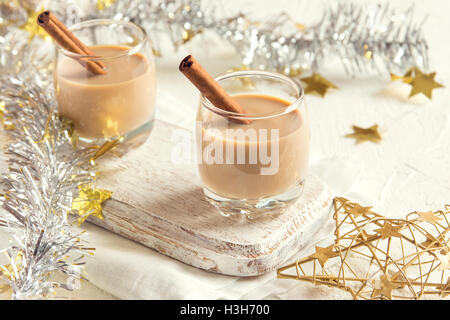 Chirstmas Eggnog with cinnamon in glasses with golden ornaments  - homemade traditional festive drink for Christmas - Stock Photo