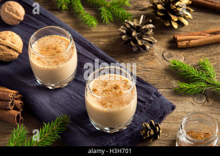 Eggnog with cinnamon in glasses over rustic wooden background with Christmas decor  - homemade Christmas festive - Stock Photo