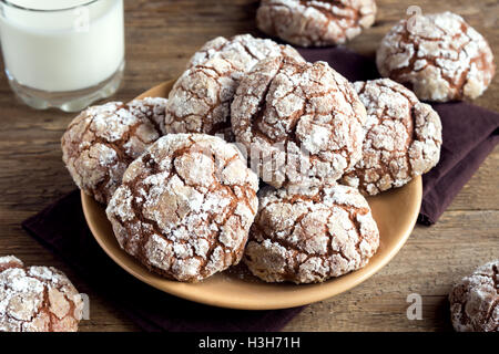 Chocolate crinkle cookies on plate with milk close up - homemade winter chocolate christmas pastry - Stock Photo