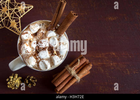 Hot chocolate with marshmallows, chocolate chips and cinnamon sticks - homemade hot festive drink for Christmas - Stock Photo