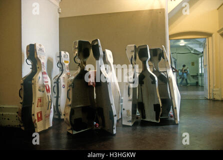 Cello cases of the London Symphony Orchestra, grouped as if they were engaged in earnest conversation, await backstage - Stock Photo